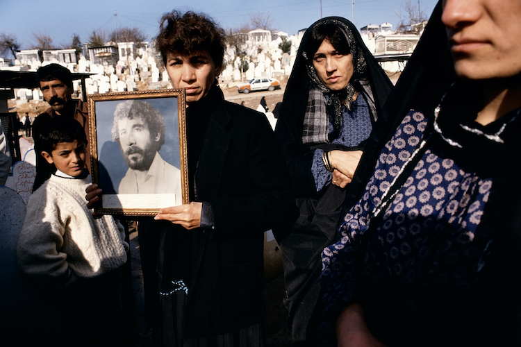 © Susan Meiselas, Photographs of 20-year-old Kamarn Saber are held by his family at Saiwan Hill cemetery. He was killed in July 1991 during a student demonstration against Saddam Hussein, Kurdistan, Northern Iraq, 1991 / © Susan Meiselas
